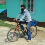 A man delivering water with a protective mask on
