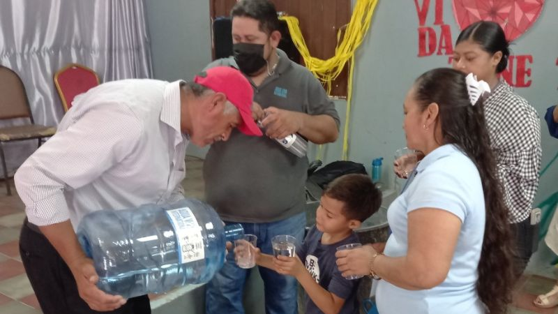 The first glass of clean water at Assembly of God Feeding Center.