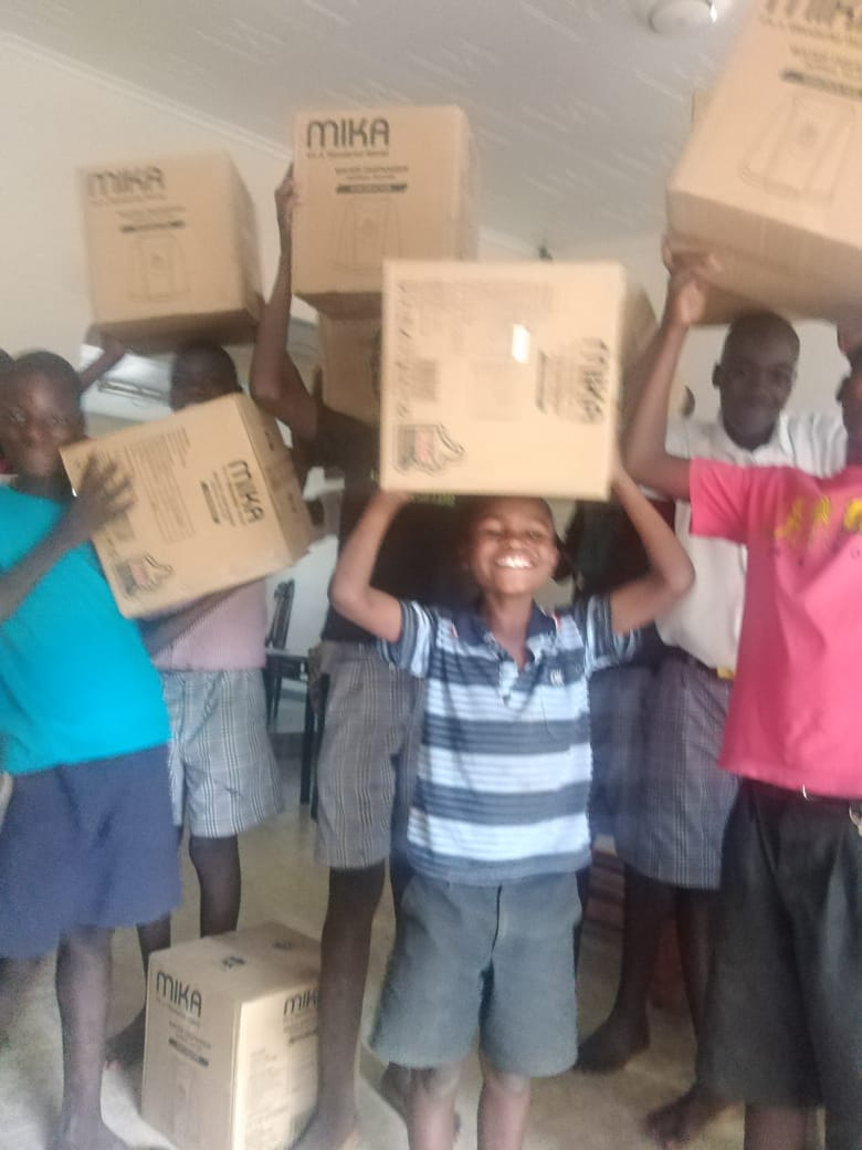 Children with boxes containing new water dispensers at Bernard's Vision
